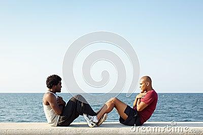 Two men exercising abs near the sea