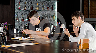 Two men friends having a drink at the bar