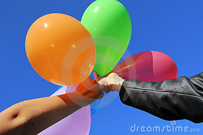 Two men holding hands with multicolored balloons
