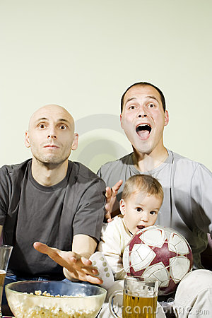 Two men and little boy watching television