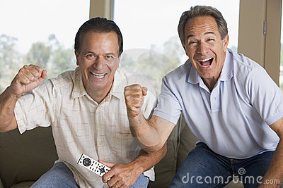 Two men in living room cheering