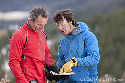 Two Men Looking at Map in the Wilderness