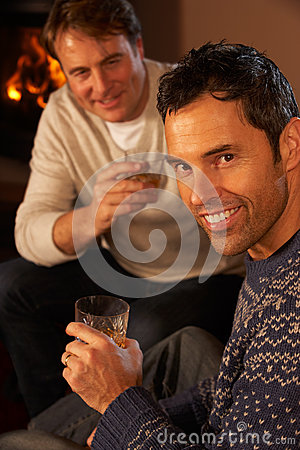 Two Men Relaxing Sitting On Sofa Drinking Whisky
