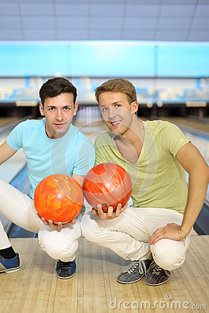Two men sit on floor with balls in bowling club