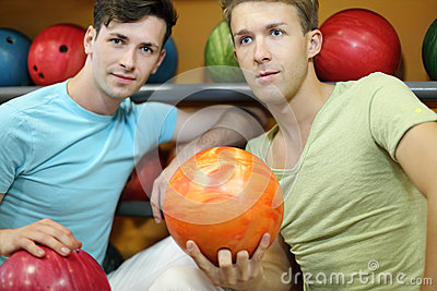 Two men sit near shelves with balls and hold balls