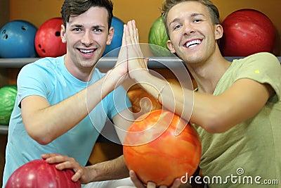 Two men sit near shelves in bowling club