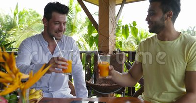 Two men sitting on summer terrace talking drink orange juice, mix race gay couple in morning on villa in tropical forest. Slow motion 60 stock video