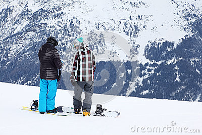 Two men with snowboards prepare for slope