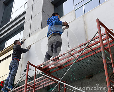 Two men stand on scaffolding and work