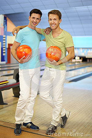 Two men stand together in bowling club