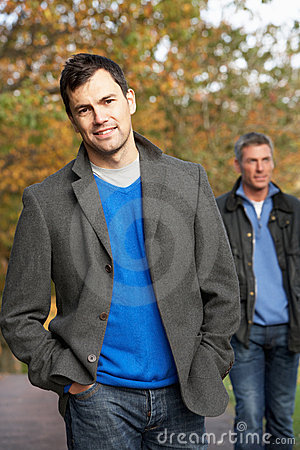Two Men Standing Outside In Autumn Woodland