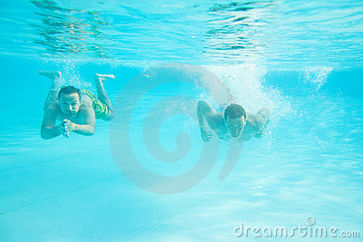 Two men swimming under water