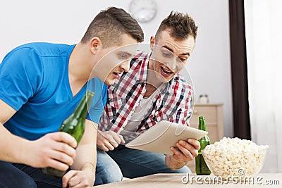 Two men watching something on tablet
