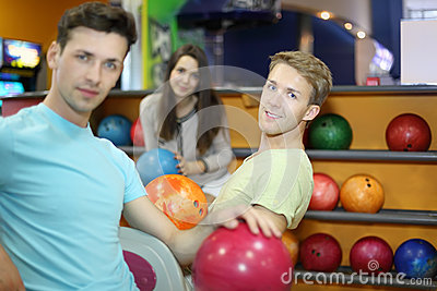 Two men and woman sit in bowling club