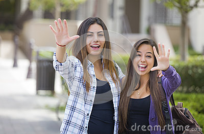 Two Mixed Race Female Students Waving with Bacpack