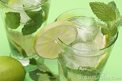 Two mojito cocktails on green background
