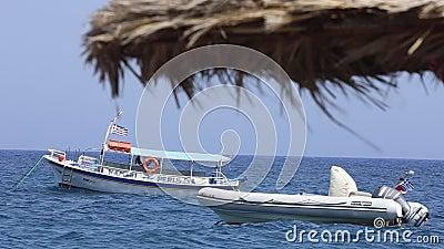 Two Moored Boats Ride the Waves Near Kamari Beach, Santorini, Greece stock video