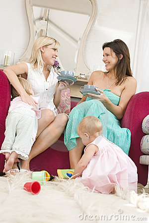 Two mothers in living room with babies and coffee
