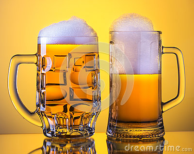 Two Mugs of fresh beer with cap of foam, on yellow back