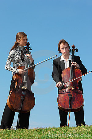 Two musicians play violoncellos against  sky
