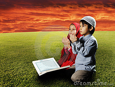 Two Muslims children sitting on meadow
