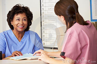Two Nurses In Discussion At Nurses Station