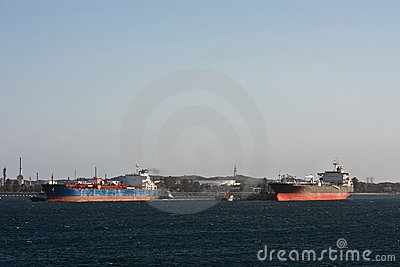 Two oil tanker ships next too each other.