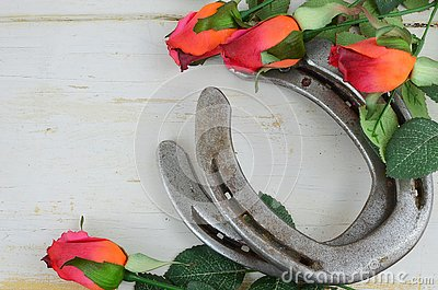 Two old horse shoes paired with silk red roses on a white-washed rustic wooden background Stock Photo