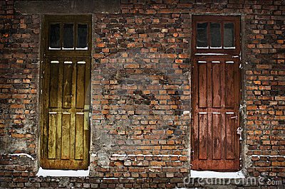 Two old wooden doors in brick wall