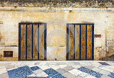 Two old wooden doors on marble brick wall colored tiled Italian garage doors
