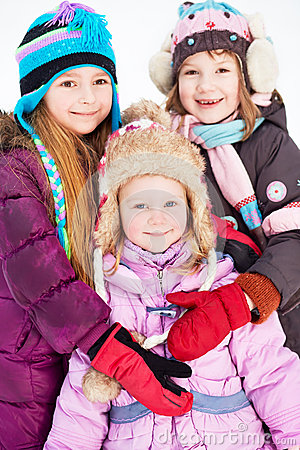Two older girls embrace younger girl standing in winter park