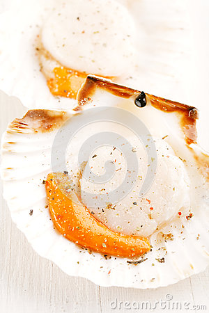 Two open scallops, topped with salt and pepper