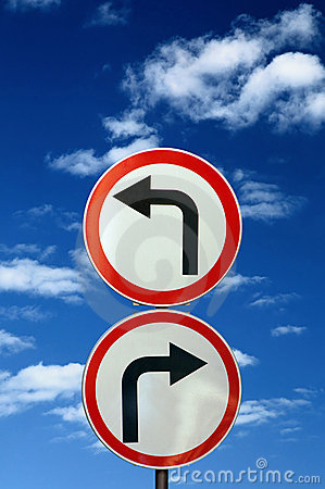 Two opposite road signs against blue sky