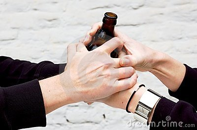 Two pairs of hands holding a dark glass