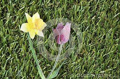 Two paper flowers on grass
