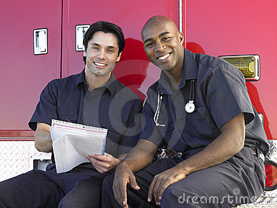Two paramedics sitting by their ambulance