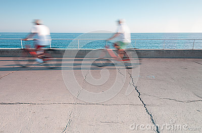 Two people on bicycles in motion.