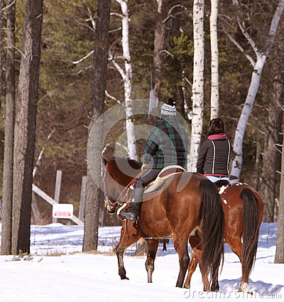Two people out horseback riding in the cold snow