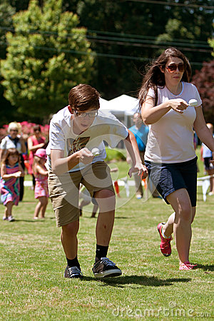 Two People Run In Egg and Spoon Race At Festival Editorial Stock Image