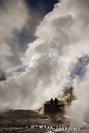Two people seated at Tatio s geyser at sunrise