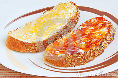 Two pieces of bread with butter and jam