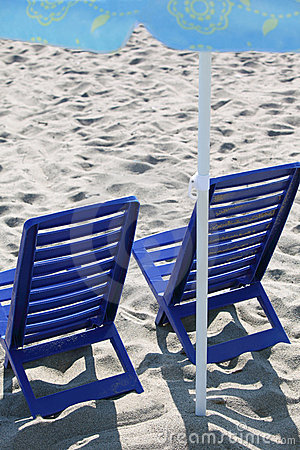Two plastic chairs stand on beach under umbrella