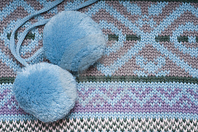 Two pompoms on knitted background