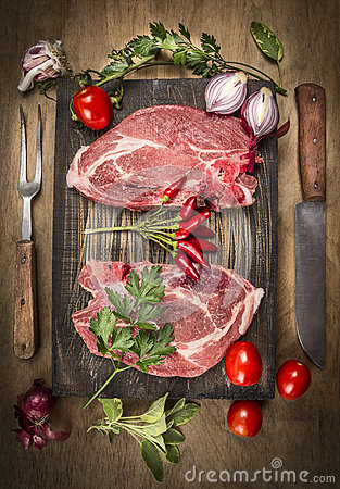 Two pork steak with meat knife and fork, fresh seasoning and spices on dark rustic wooden background, top view Stock Photo