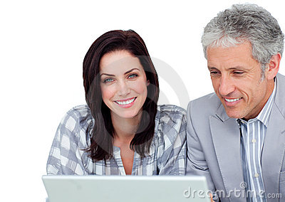 Two positive business co-workers using a laptop