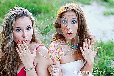 Two pretty caucasian girls surprised