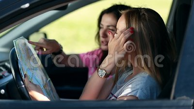 Two pretty girls in car paving travel route on map stock video footage