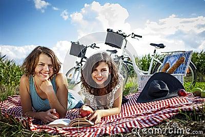 Two pretty girls make a picnic, reading a book