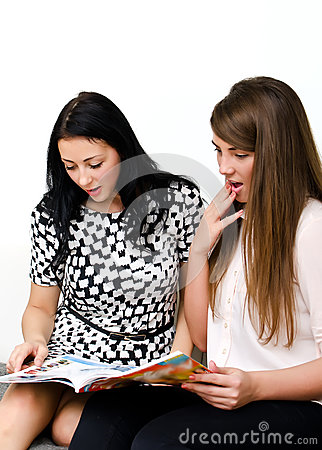 Two pretty girls reading magazine