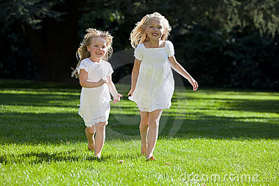 Two Pretty Young Girls Running In A Green Park